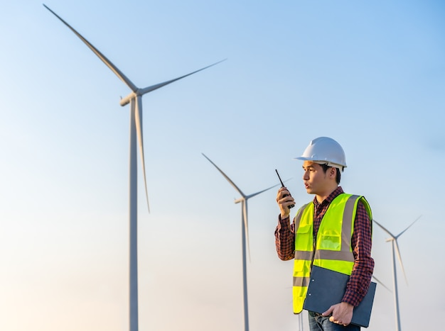 Young male engineer using walkie talkie to checking system against wind turbine farm