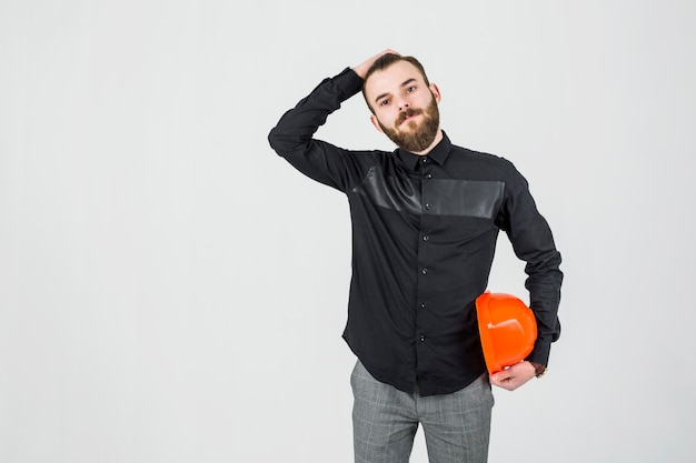 Young male engineer with hand on his head holding hardhat