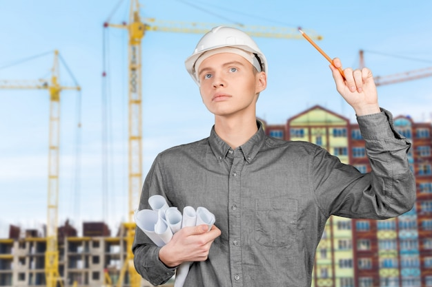 Young male engineer with helmet holding blueprints