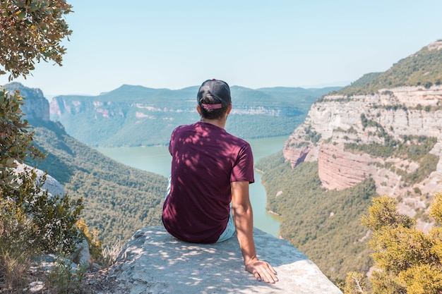 Young male enjoying the mesmerizing scenery of the morro de la abeja in tavertet, catalonia, spain