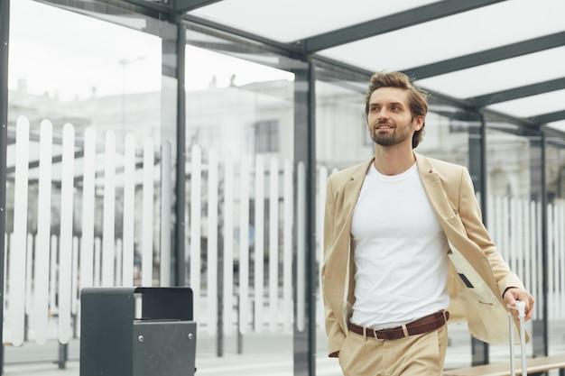 駅でスーツケースを運ぶ流行のビジネススーツに身を包んだ若い男性起業家。屋外でバスを待っているひげを生やした男