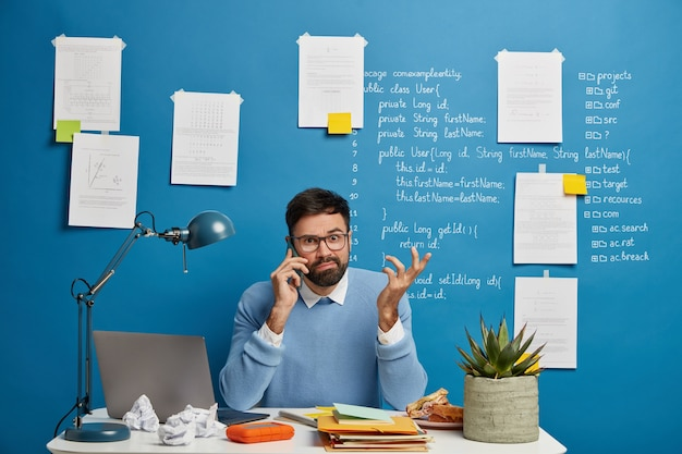 Young male entrepreneur thinks on business solution during telephone conversation, raises hand confusingly, sits at white desk with notepads, crumpled paper and laptop computer