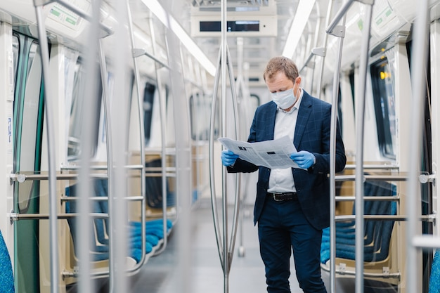 Young male entrepreneur wears disposable medical mask and gloves in metro, prevents coronavirus disease, poses in empty carriage, reads newspaper, finds out information about contagious virus