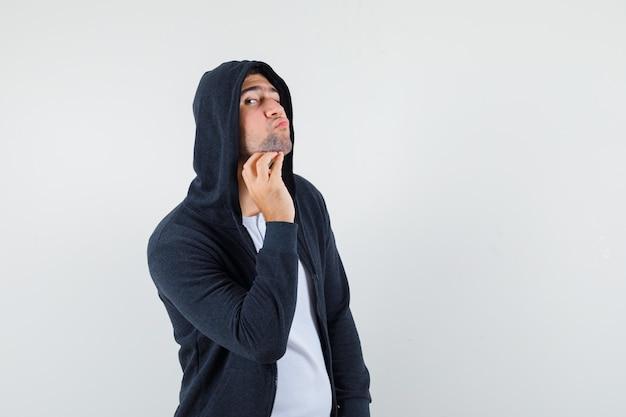 Молодой мужчина осматривает кожу, касаясь его бороды в куртке, футболке и выглядит красивым, вид спереди.
