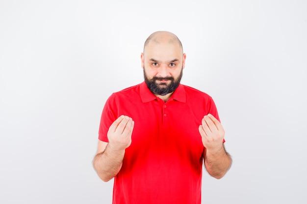 Giovane maschio che spiega qualcosa nella vista frontale della camicia rossa.