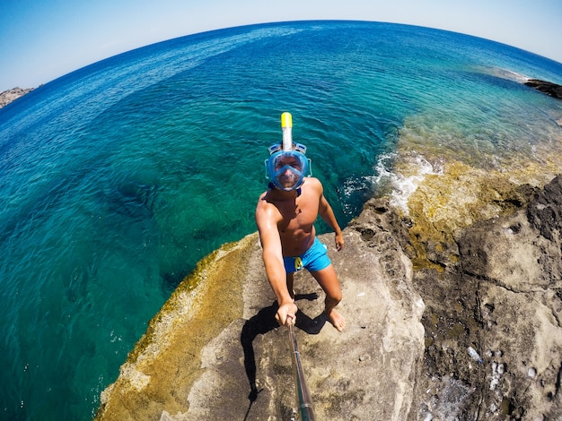 Young male explorer in adventure ready for snorkeling. selfie shot at summer day at rock in the middle of the sea.