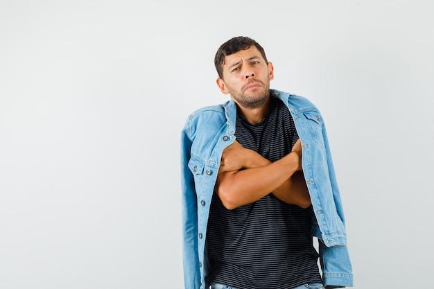 若い男性がtシャツのジャケットで冷たく感じる