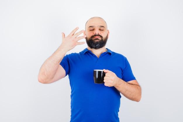 青いシャツに新鮮な匂いを感じ、満足そうな若い男性、正面図。