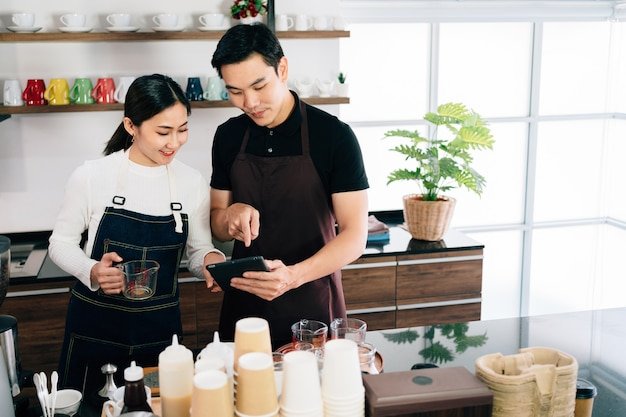 Young male and female barista cafe owner standing inside the coffee counter and talking about customer order from a tablet with smiles.