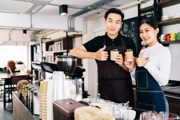Young male and female barista cafe owner standing inside the coffee counter.