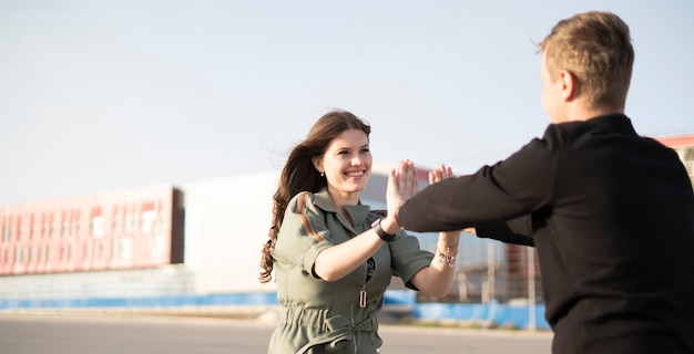 A young male and female couple give high five outdoors, success happy relationship concept