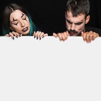 Giovane maschio e femmina che tiene ampio strato bianco