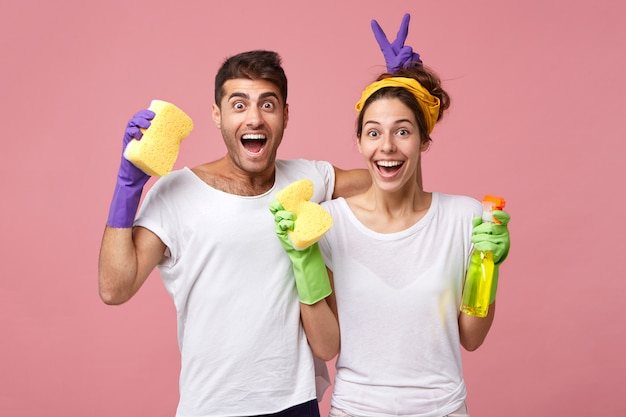Young male and female playing fools while standing against white pink wall resting