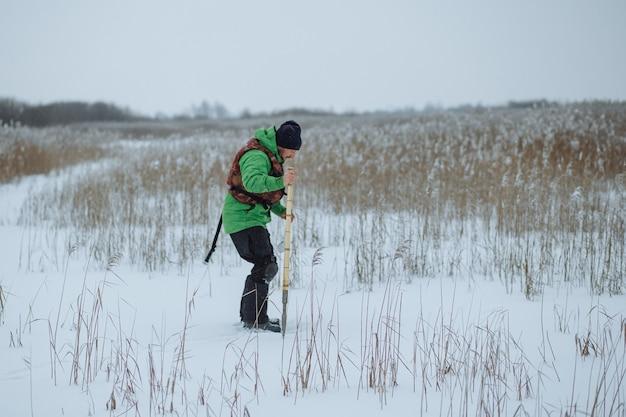 Молодой рыбак делает яму в заснеженном озере