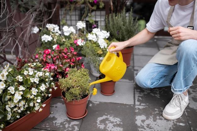 Giovane fiorista maschio che innaffia le piante