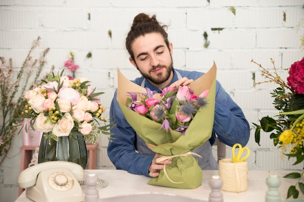 Young male florist wrapping the flower bouquet in the flower shop