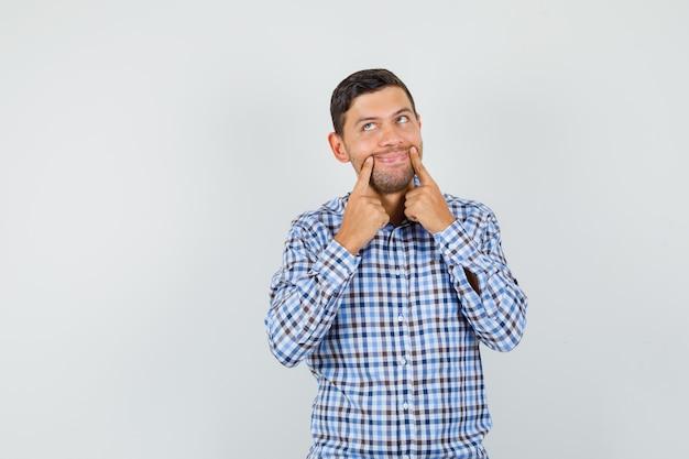 Giovane maschio che costringe un sorriso sul viso in camicia a quadri