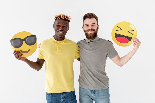 Young male friends holding emoji