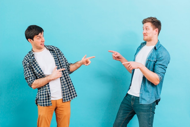 Young male friends making funny faces pointing fingers to each other against blue background