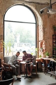 Молодые друзья-мужчины отдыхают в кафе-лофте и обсуждают последние приложения с помощью современных устройств