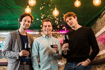 Young male friends with wine glasses enjoying in party at bar