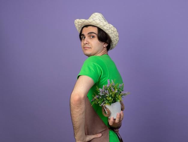 허리에 화분에 꽃을 들고 원예 모자를 쓰고 제복을 입은 젊은 남성 정원사