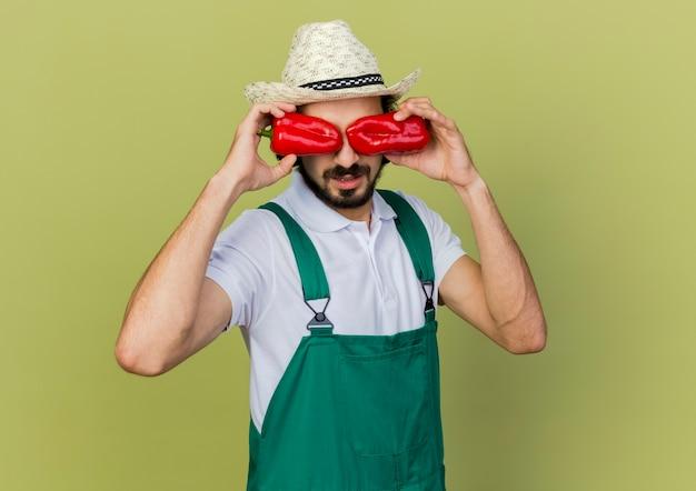 Il giovane giardiniere maschio in vetri ottici che porta il cappello di giardinaggio chiude gli occhi con i peperoni rossi
