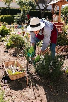 Молодой мужчина садовник, посадка растений в саду
