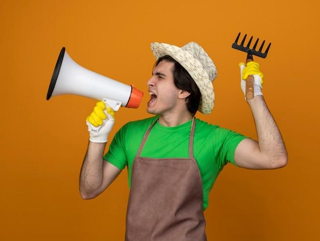 Young male gardener in uniform wearing gardening hat with gloves with closed eyes speaks on loudspeaker raising rake isolated on orange