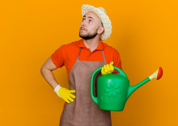 원예 모자를 쓰고 젊은 남성 정원사는 허리에 손을 넣고 측면을보고 물을 수 있습니다.