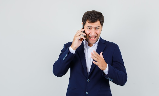 Young male getting angry while talking on smartphone in suit , front view.