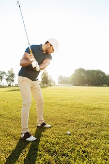 Young male golfer hitting ball with a club