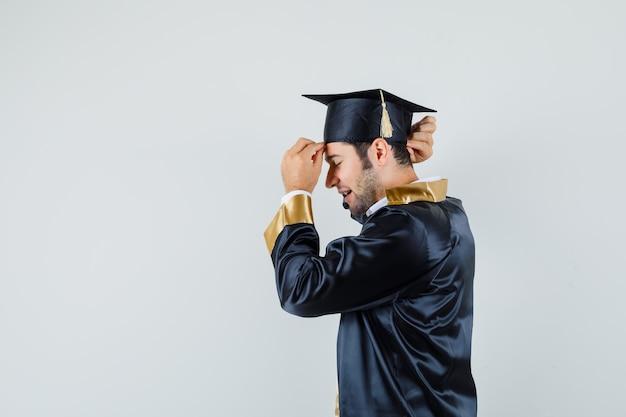 Giovane maschio in uniforme laureato che adegua il suo berretto nero e sembra bello.