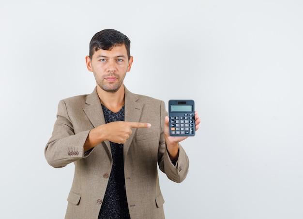 Giovane maschio in giacca marrone grigiastro, camicia nera che punta alla calcolatrice e che guarda attento, vista frontale.