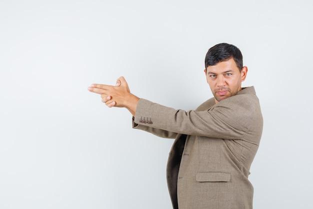 Giovane maschio in giacca marrone grigiastro che mostra il gesto della pistola e che sembra fiducioso, vista frontale.