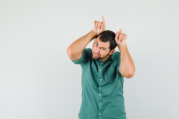 Giovane maschio in camicia verde che tiene le dita sopra la testa come corna di toro e sembra divertente, vista frontale.