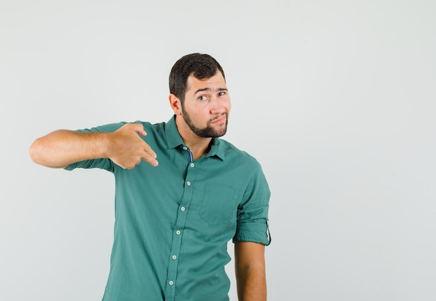 Young male in green shirt making pistol gesture , front view.