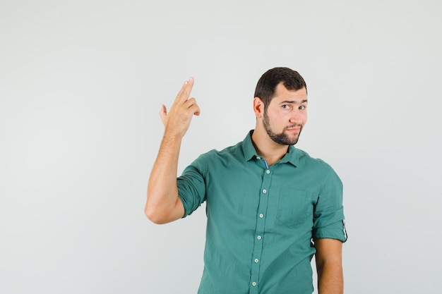 Young male in green shirt showing pistol gesture and looking cute , front view.