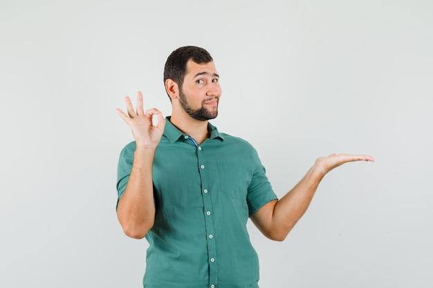 Giovane maschio in camicia verde che allarga il palmo da parte mentre mostra un gesto ok e sembra contento, vista frontale.