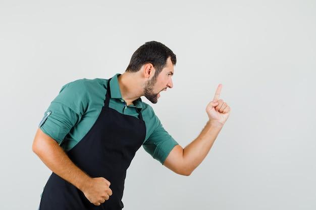 Giovane maschio in camicia verde che avverte qualcuno con il dito e sembra arrabbiato, vista frontale.