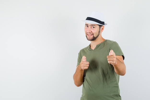 Young male in green t-shirt and hat pointing at camera and looking confident