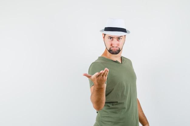 Giovane maschio in maglietta verde e cappello alzando la mano in modo interrogativo e guardando strano