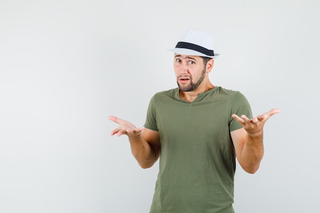 Young male in green t-shirt and hat raising hands in questioning manner and looking confused