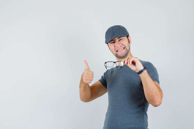 Young male in grey t-shirt cap holding glasses showing thumb up and looking happy