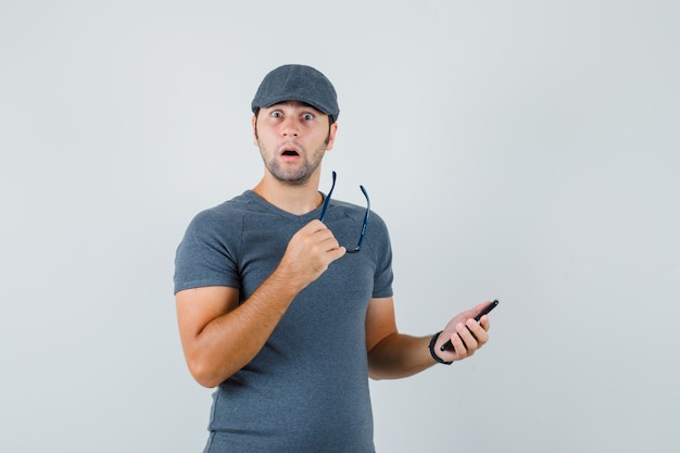 Young male in grey t-shirt cap holding mobile phone and glasses and looking surprised