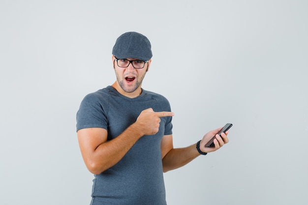 Giovane maschio in cappuccio grigio della maglietta che indica al telefono cellulare e che osserva stupito