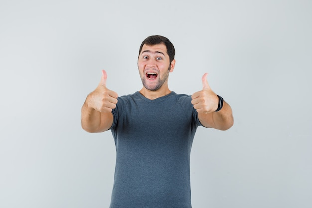 Young male in grey t-shirt showing double thumbs up and looking cheery