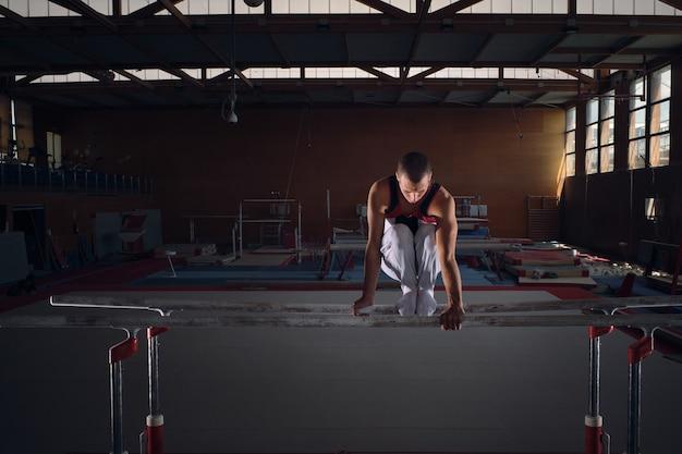 並列装置でエクササイズをしている若い男性の体操選手。