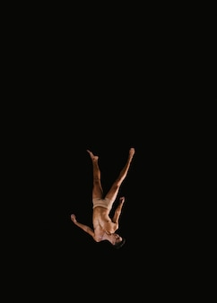 Young male gymnast flying upside down
