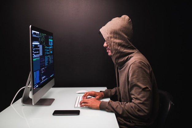 Young male hacker in dark room writing code or using computer virus program for cyber attack